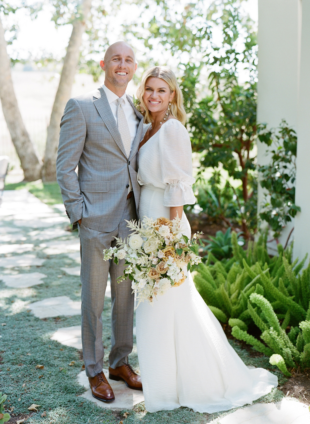 bride and groom smiling outside on stone pathway