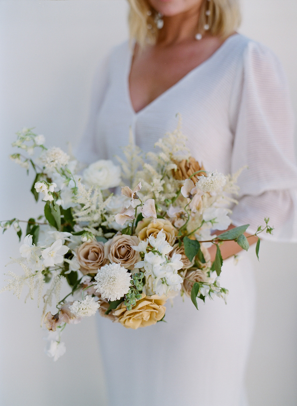 bride holding white and neutral hued floral wedding bouquet