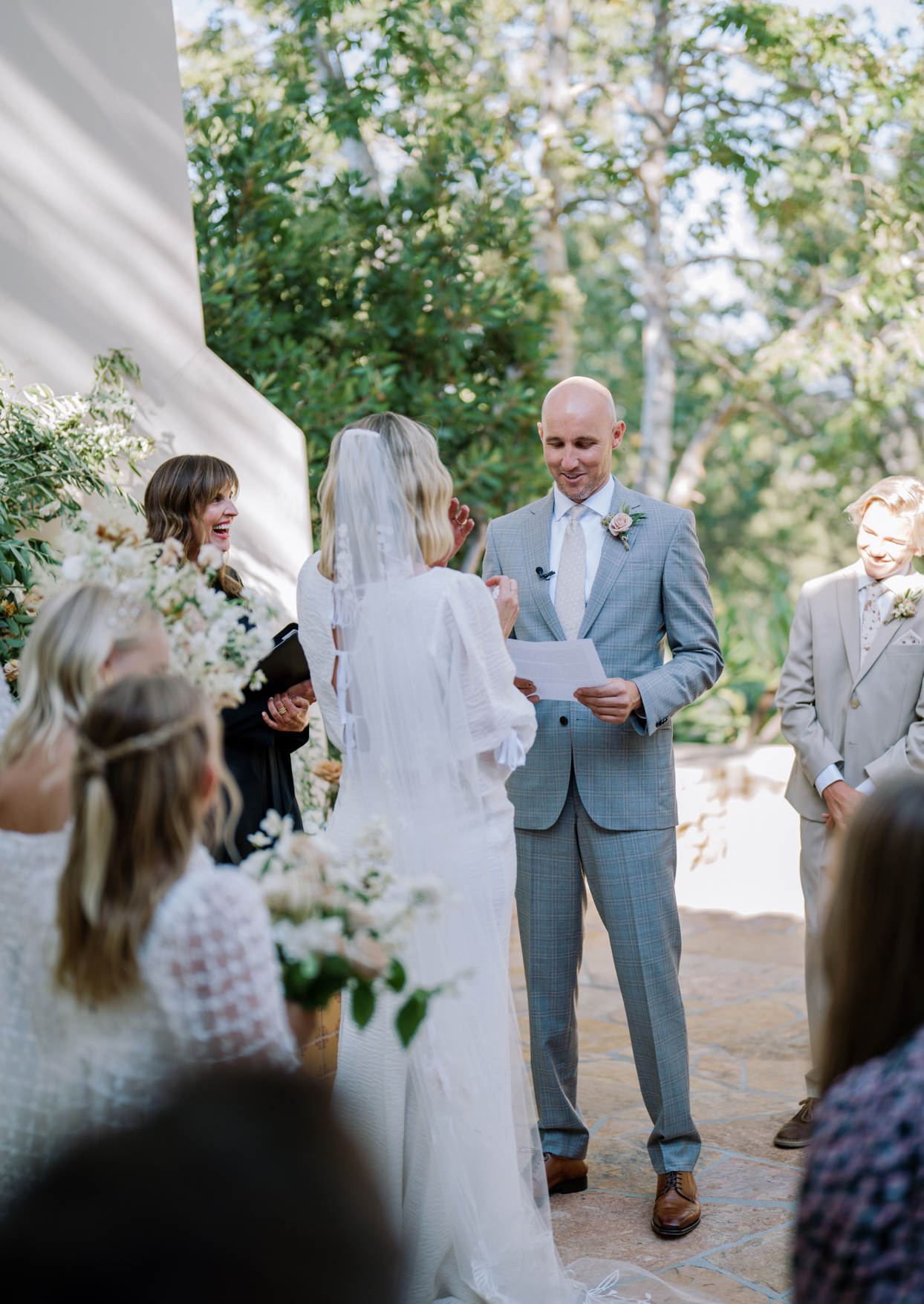 groom smiling reading wedding vows