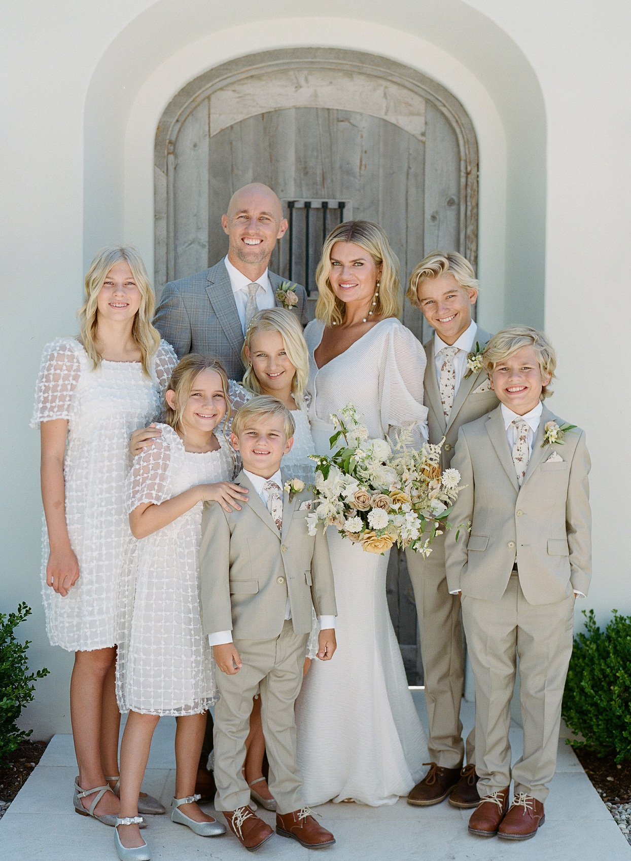 bride and groom standing with blended family