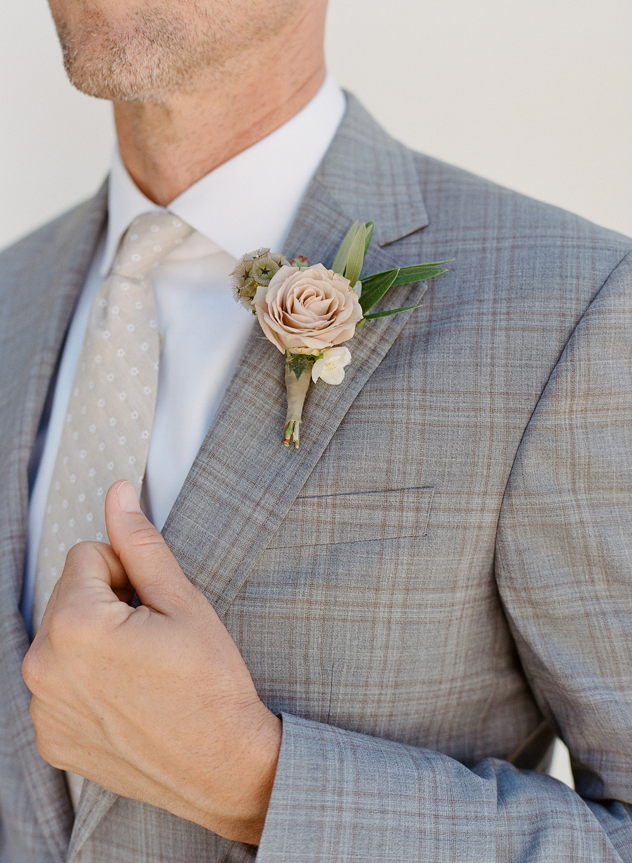 groom wearing pale grey and tan plaid suit
