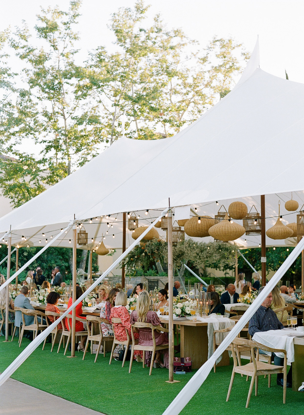 large white tent with wicker lanterns hanging
