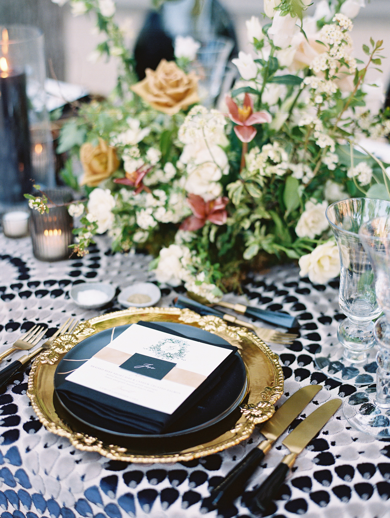 table setting with gold charger and black plate