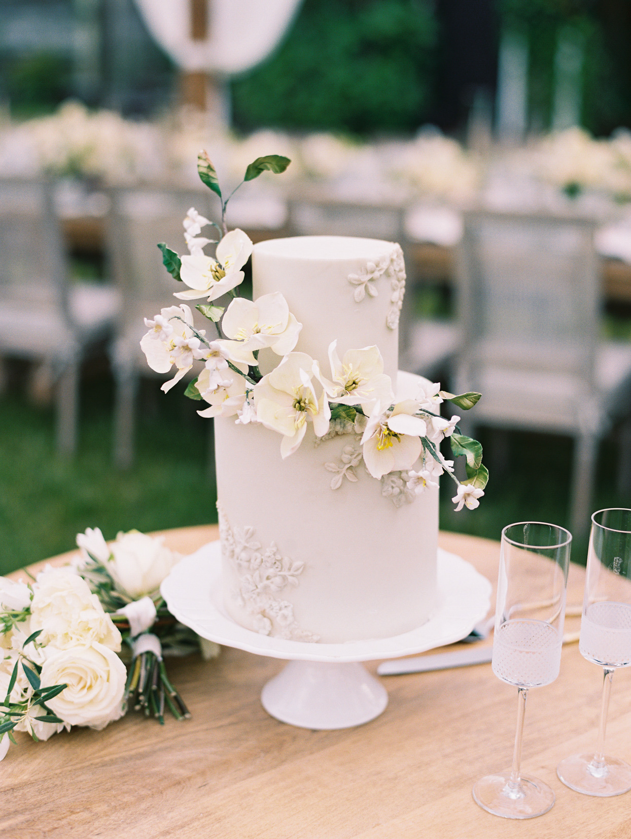 two tiered white frosted wedding cake with white flower accent