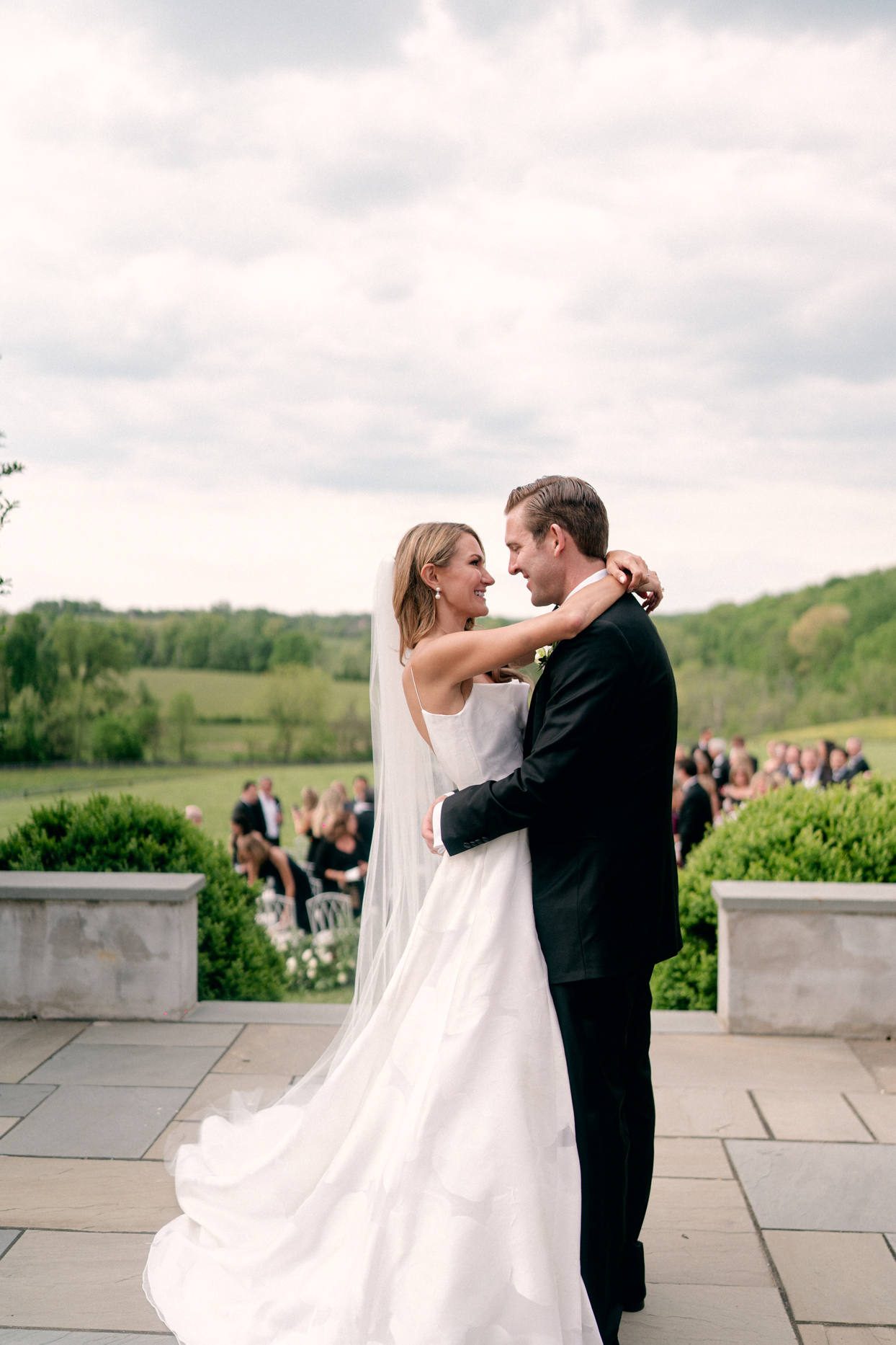 bride and groom smiling during embrace on stone patio