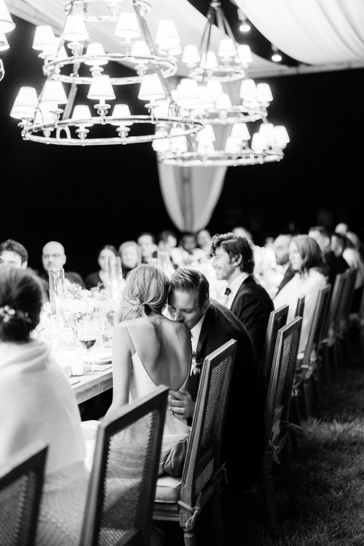 groom kisses wifes shoulder sitting at reception table