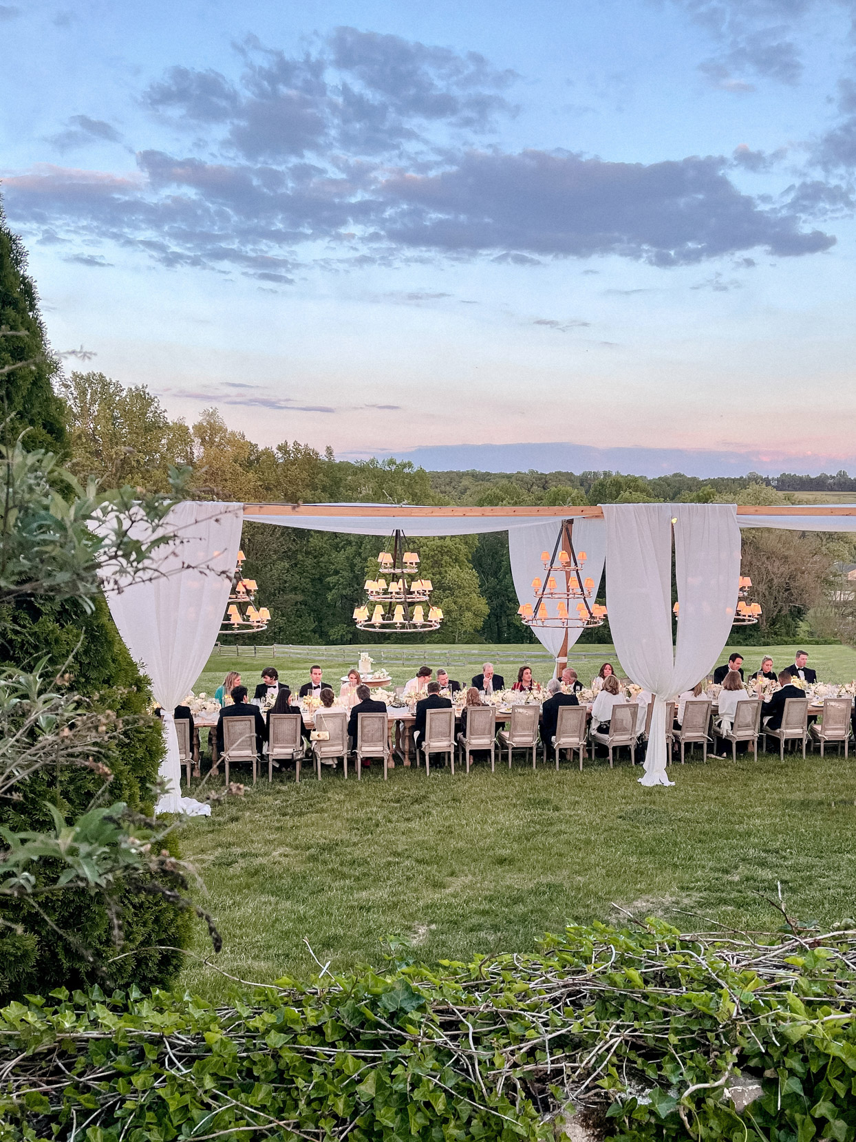 wedding guests sit at extended long reception table outside