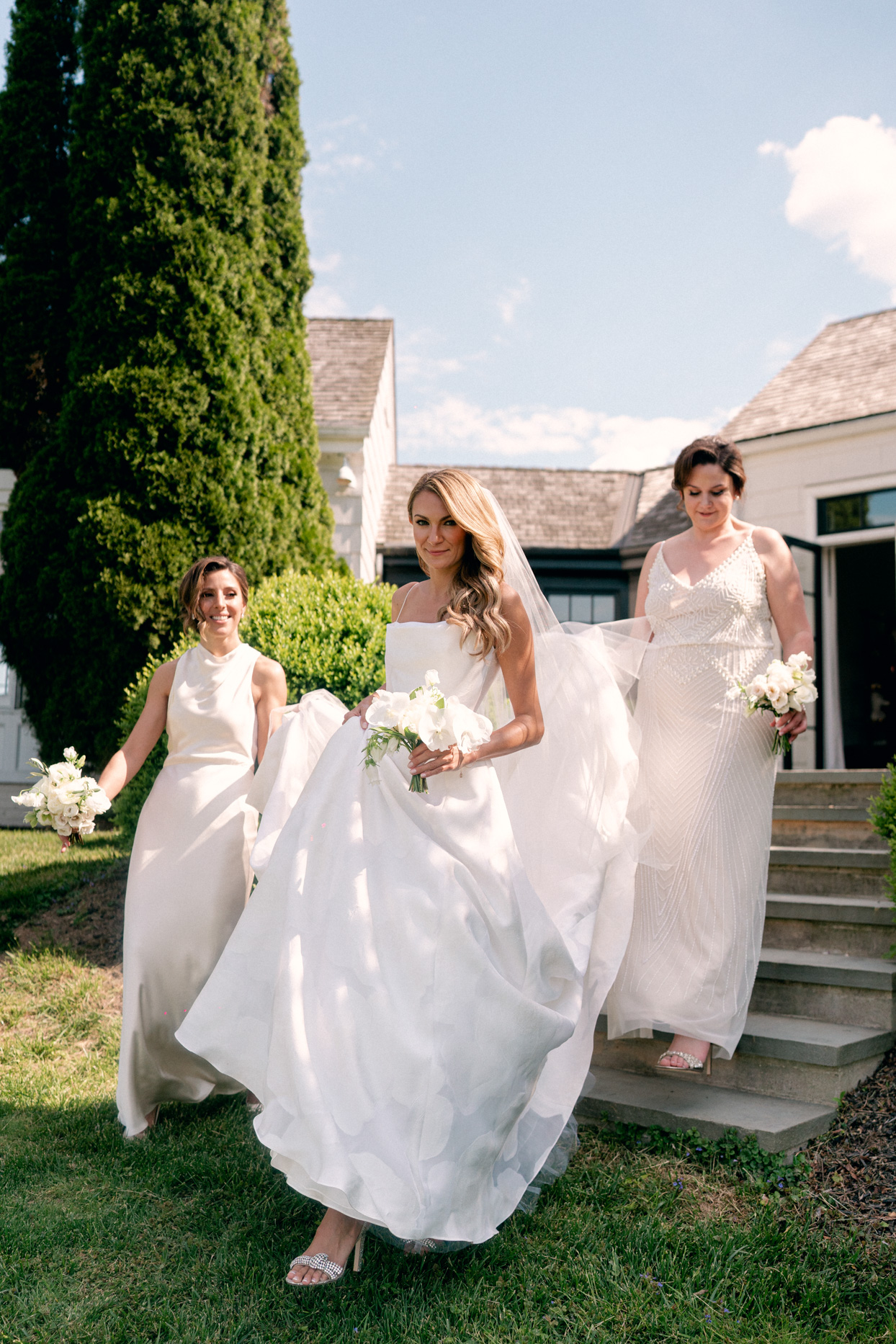 bridesmaids walking with bride carrying her dress