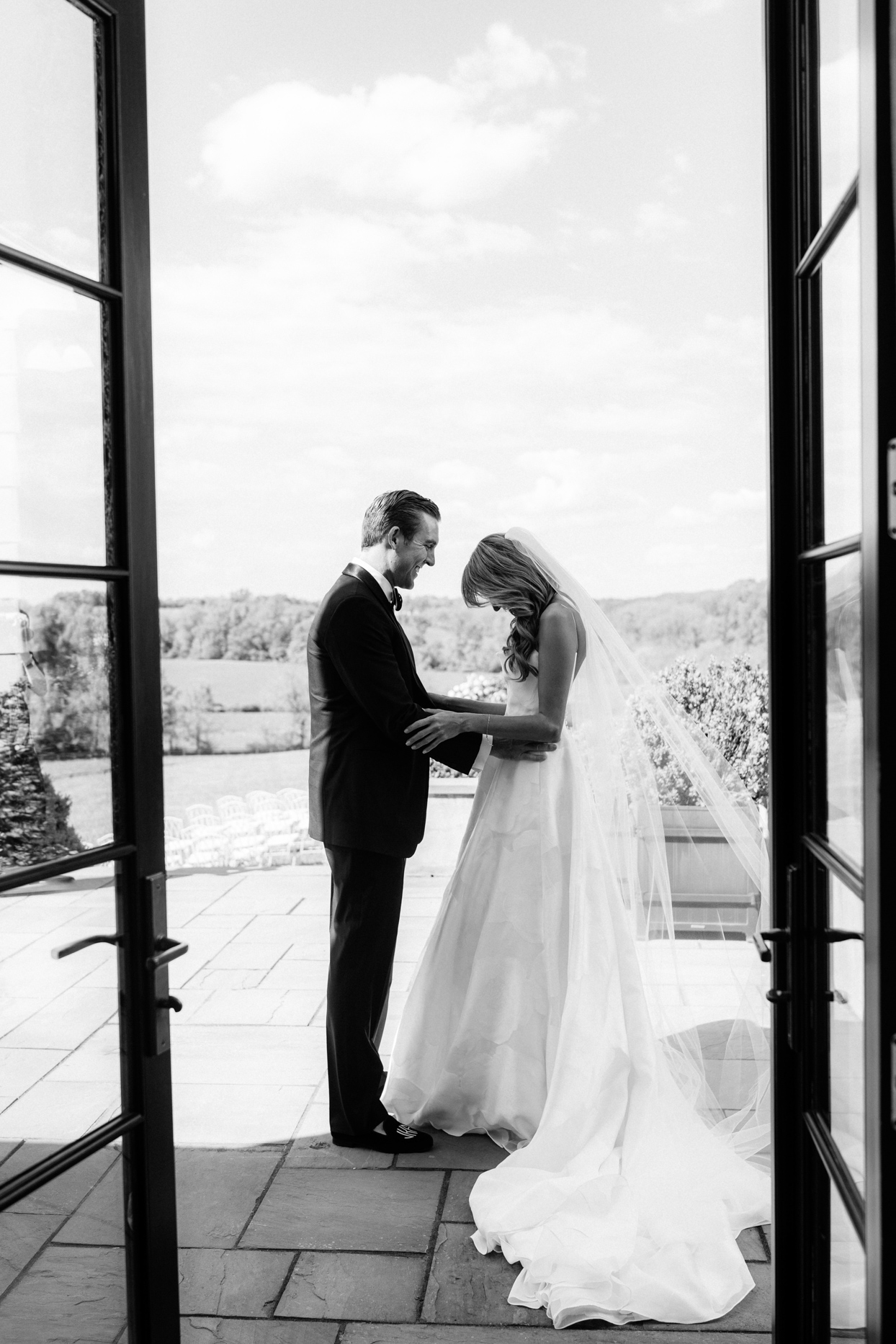 groom smiling at bride during first look on stone patio