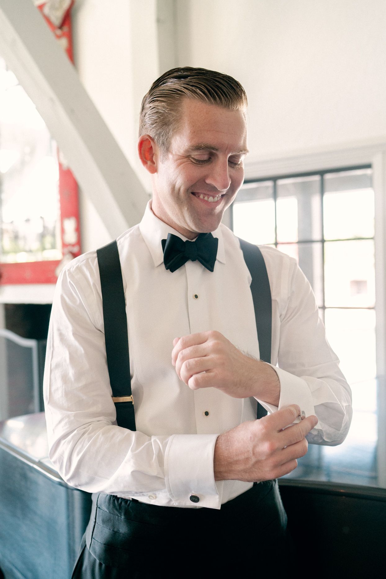 groom smiling wearing black and white suit with bowtie