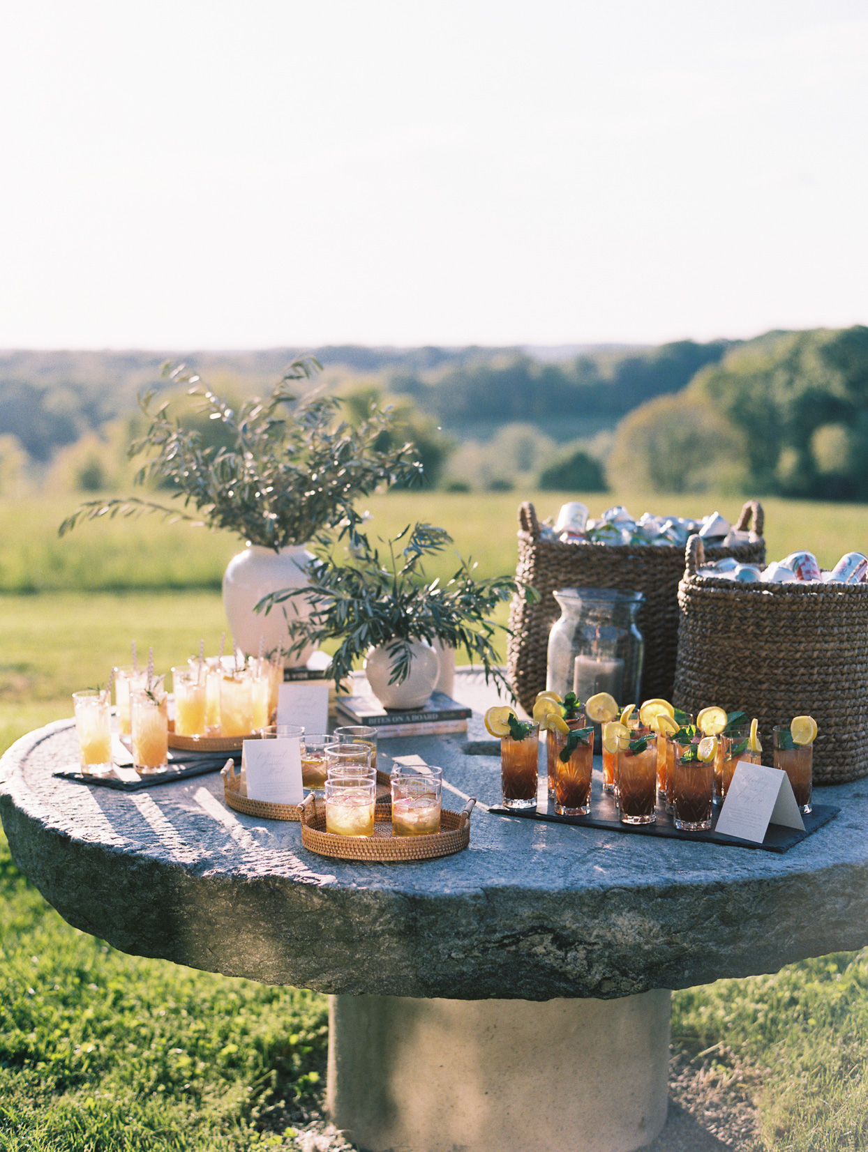 stone table topped with various cocktails and drinks for welcome dinner