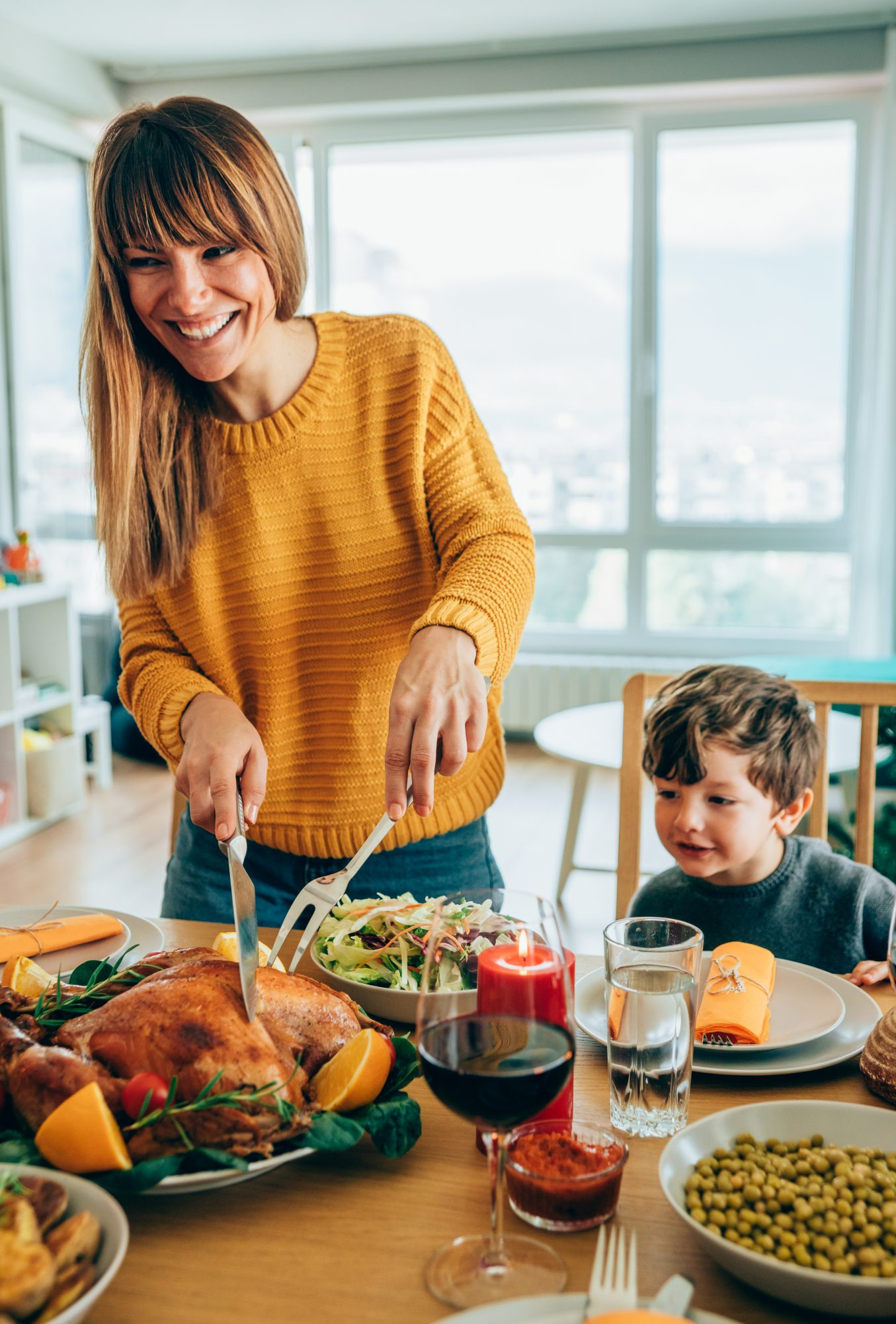 woman carving thanksgiving turkey at table