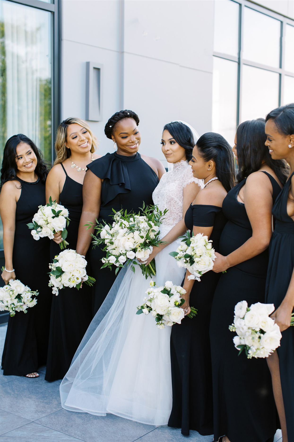 bride standing with bridesmaids wearing black dresses