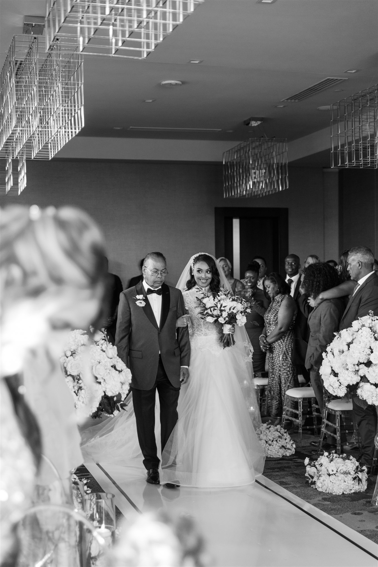 bride smiling walking down processional with father
