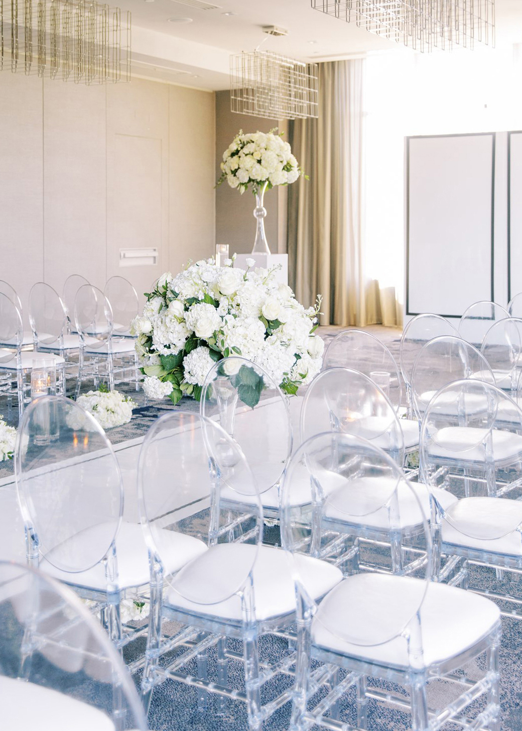 clear wedding ceremony chairs lined ballroom space