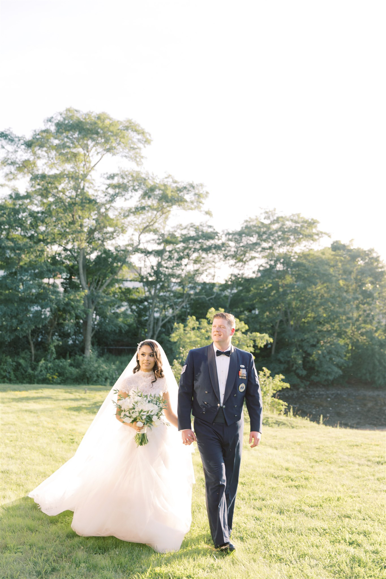 bride and groom smiling walking on grass outside