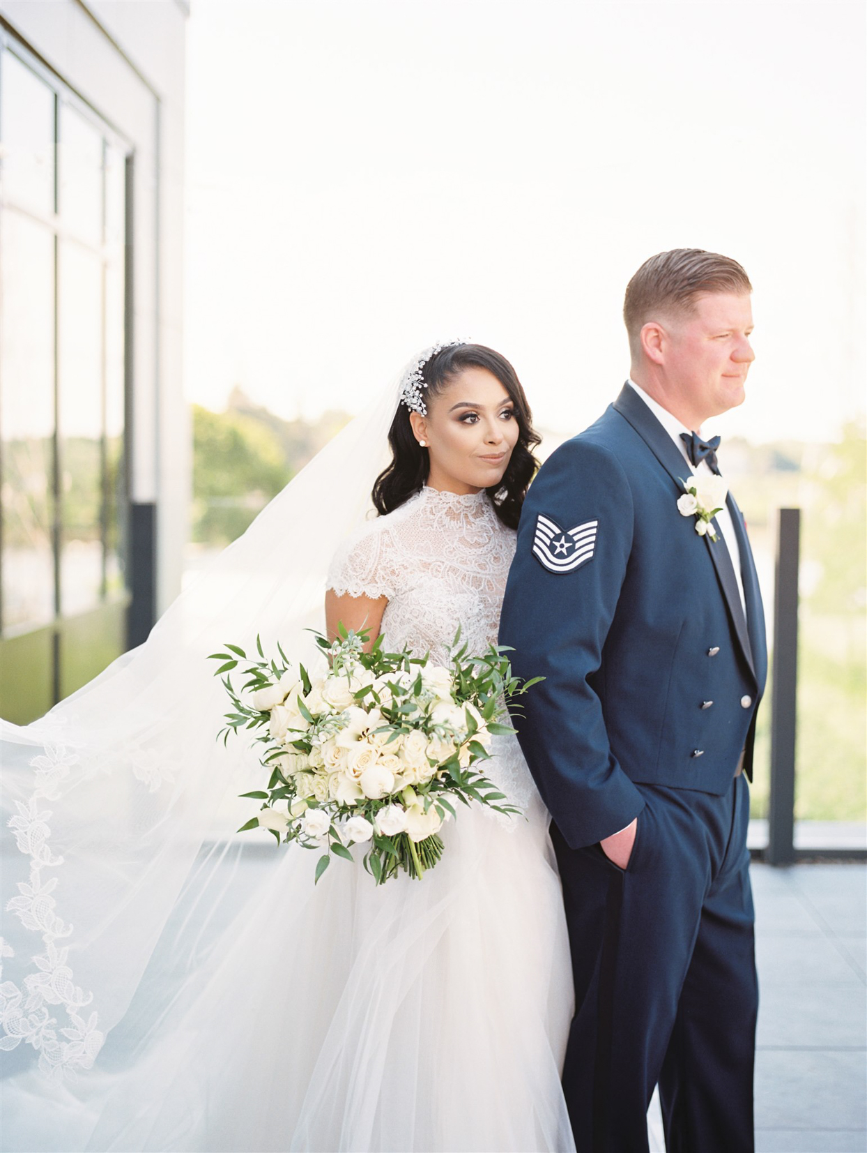 bride and groom standing on balcony outside