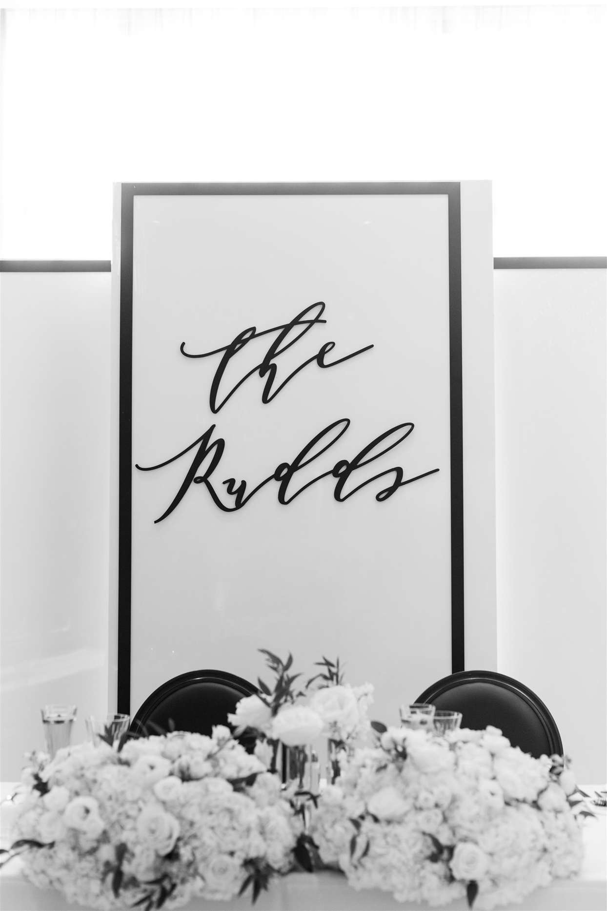 black and white last name wedding sign at sweetheart table