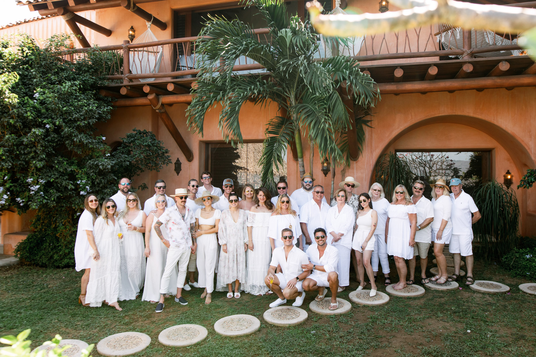 wedding couple and guests all dressed in white for tropical brunch