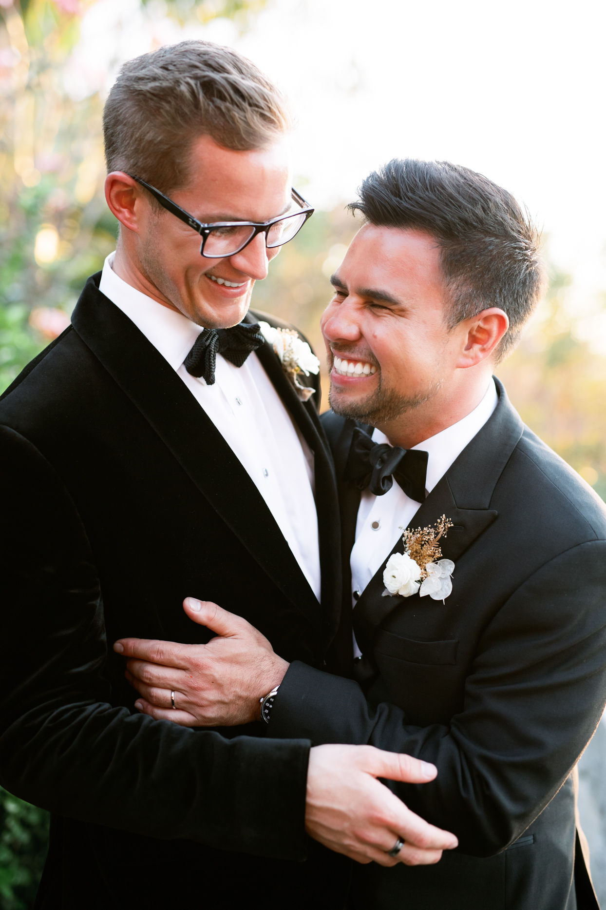 close up couple portrait in black suits laughing