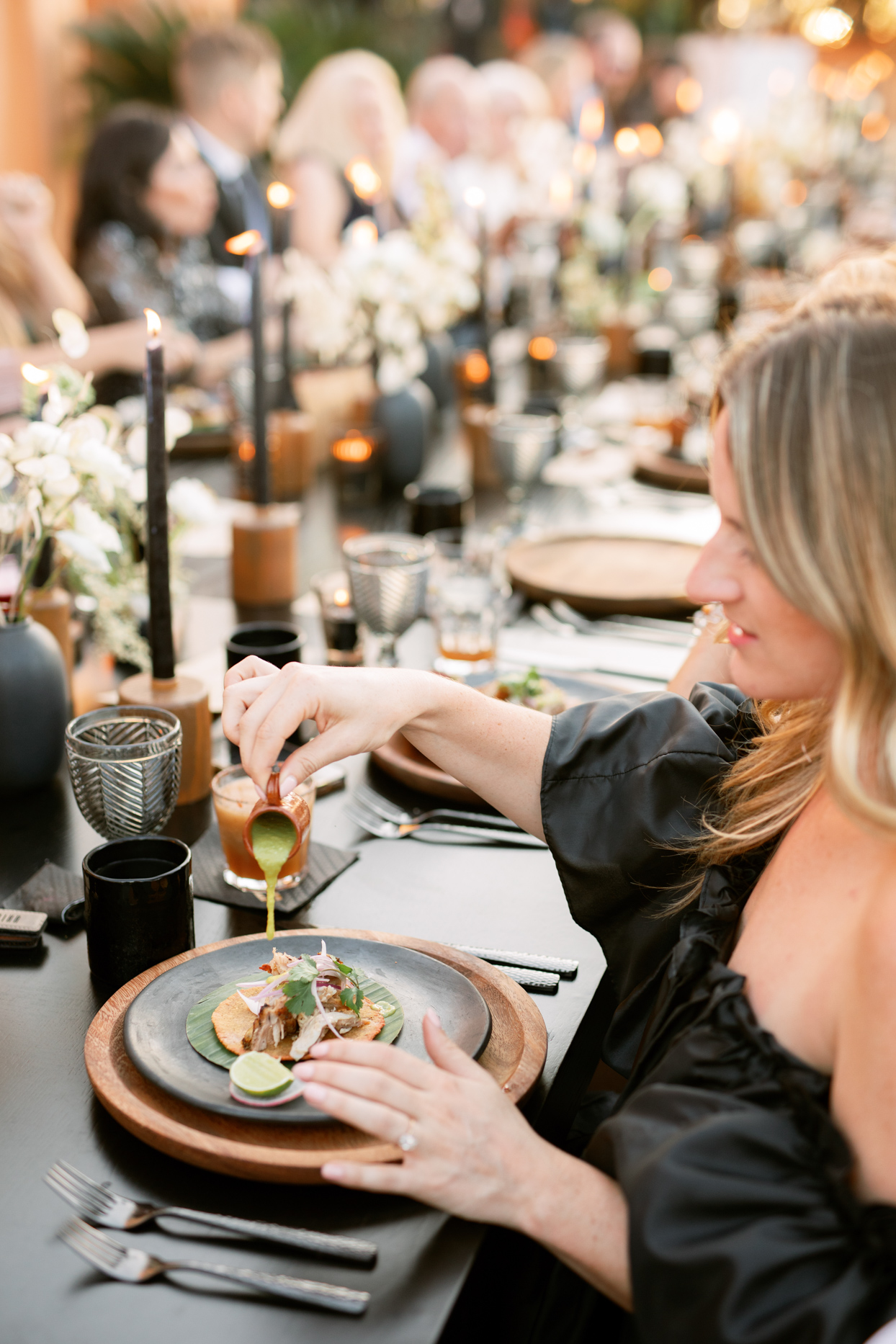 guesting pouring sauce on elegant wedding taco at reception