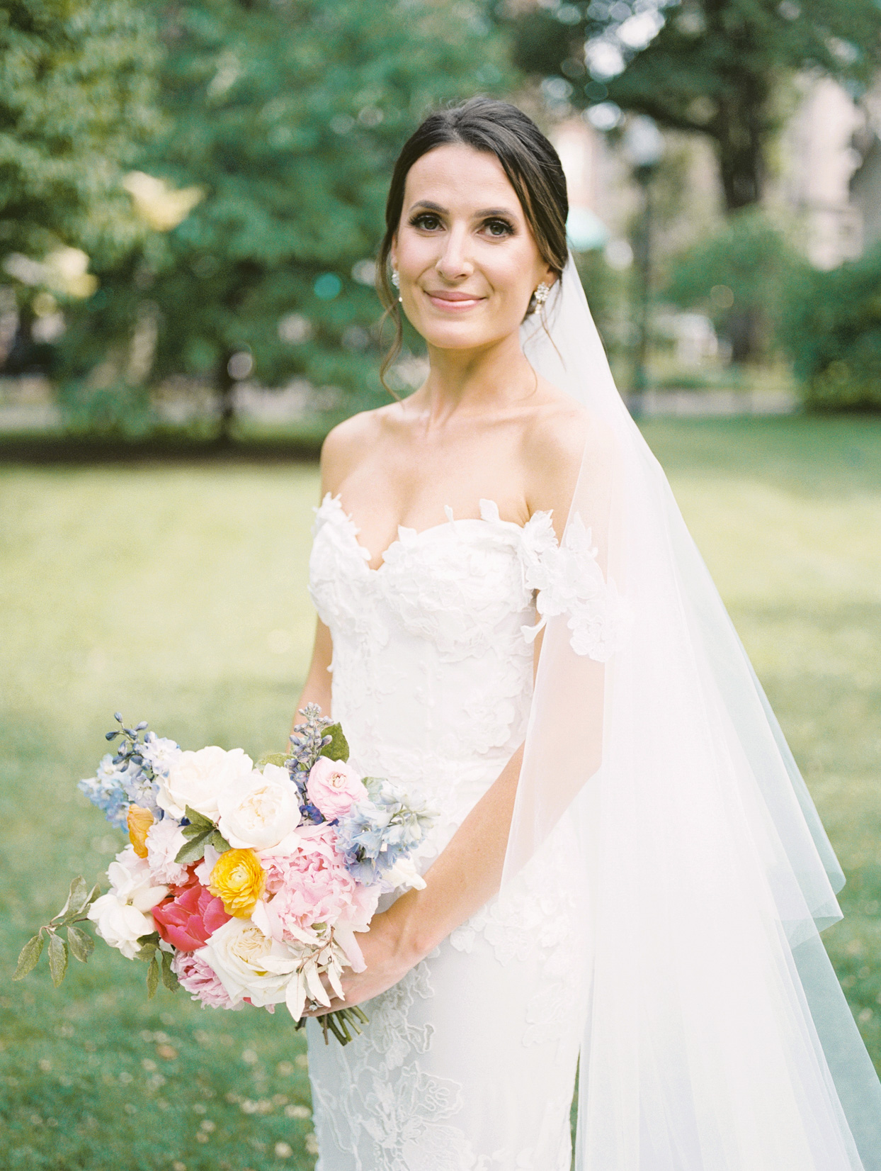 bride wearing wedding dress with sweetheart neckline, fitted bodice, off-the-shoulder straps, and dramatic train