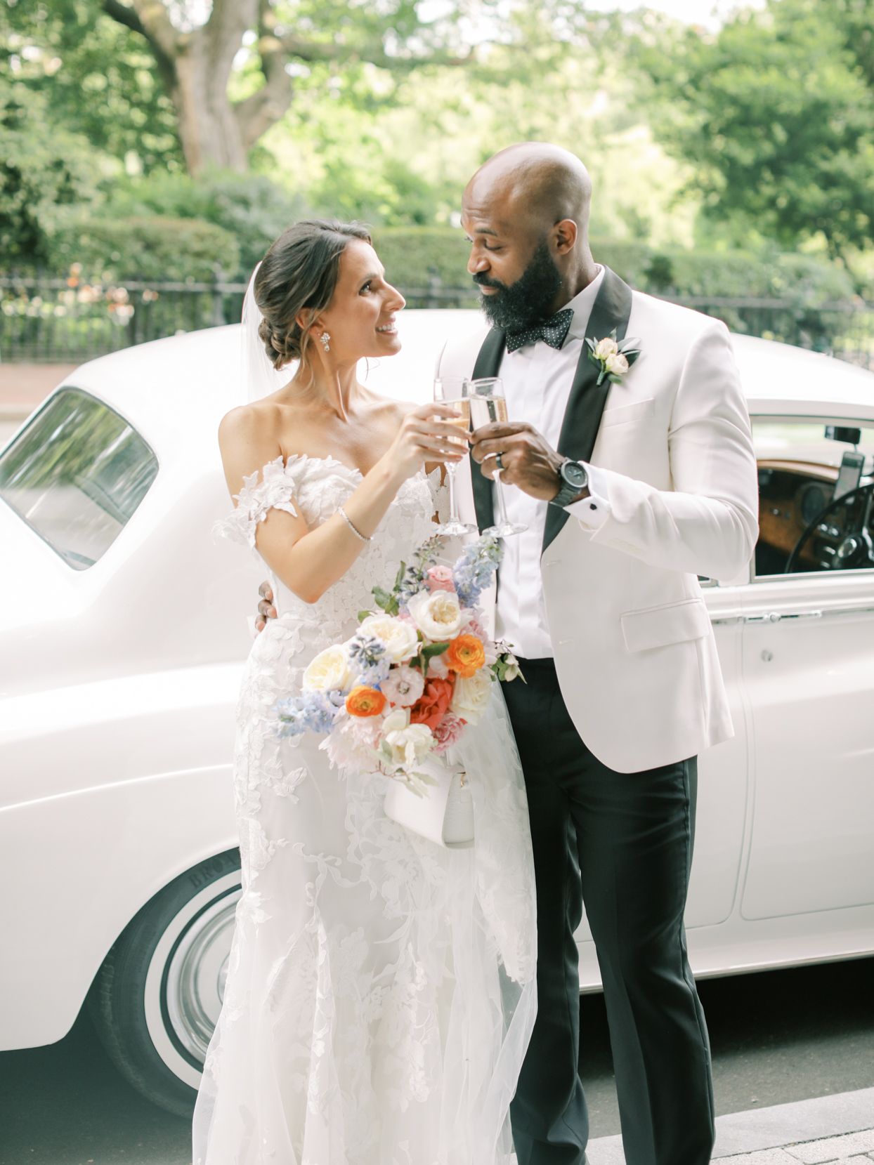 bride and groom toasting in front of car