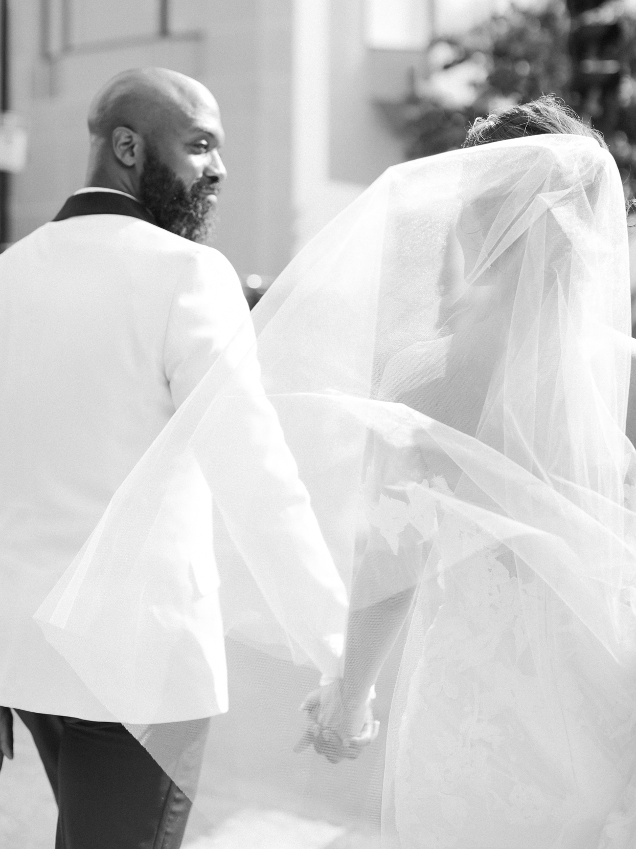 bride and groom looking at each other while walking