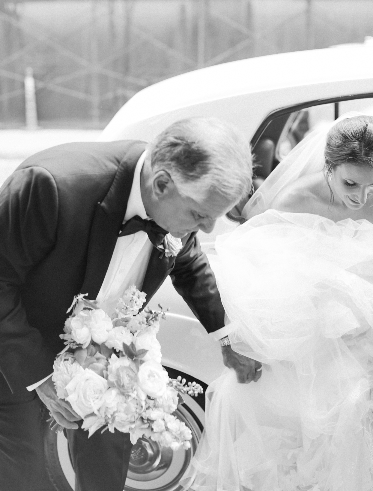 father helping bride out of car