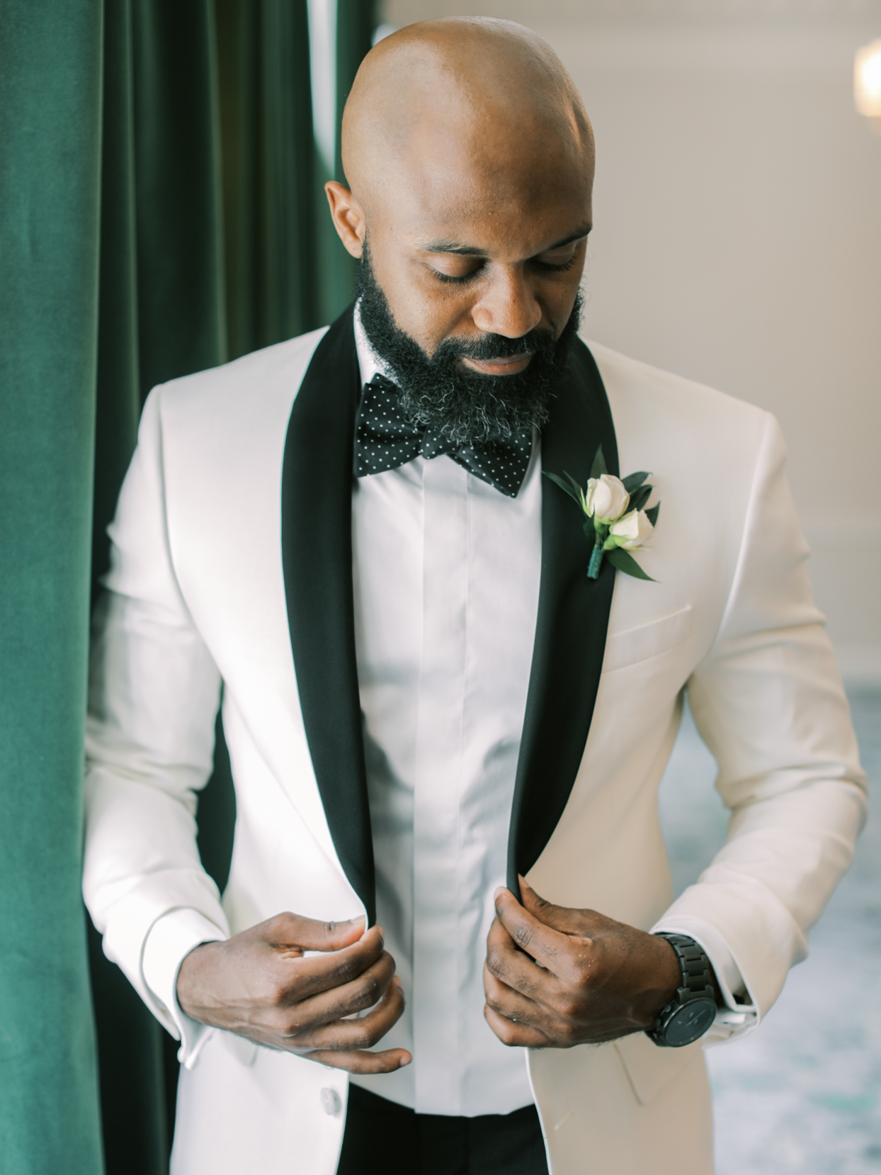 groom wearing a white dinner jacket and tuxedo