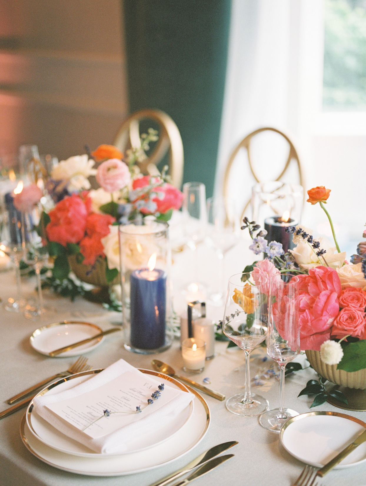 wedding reception place settings with gold-rimmed chargers, gold flatware, and navy pillar candles