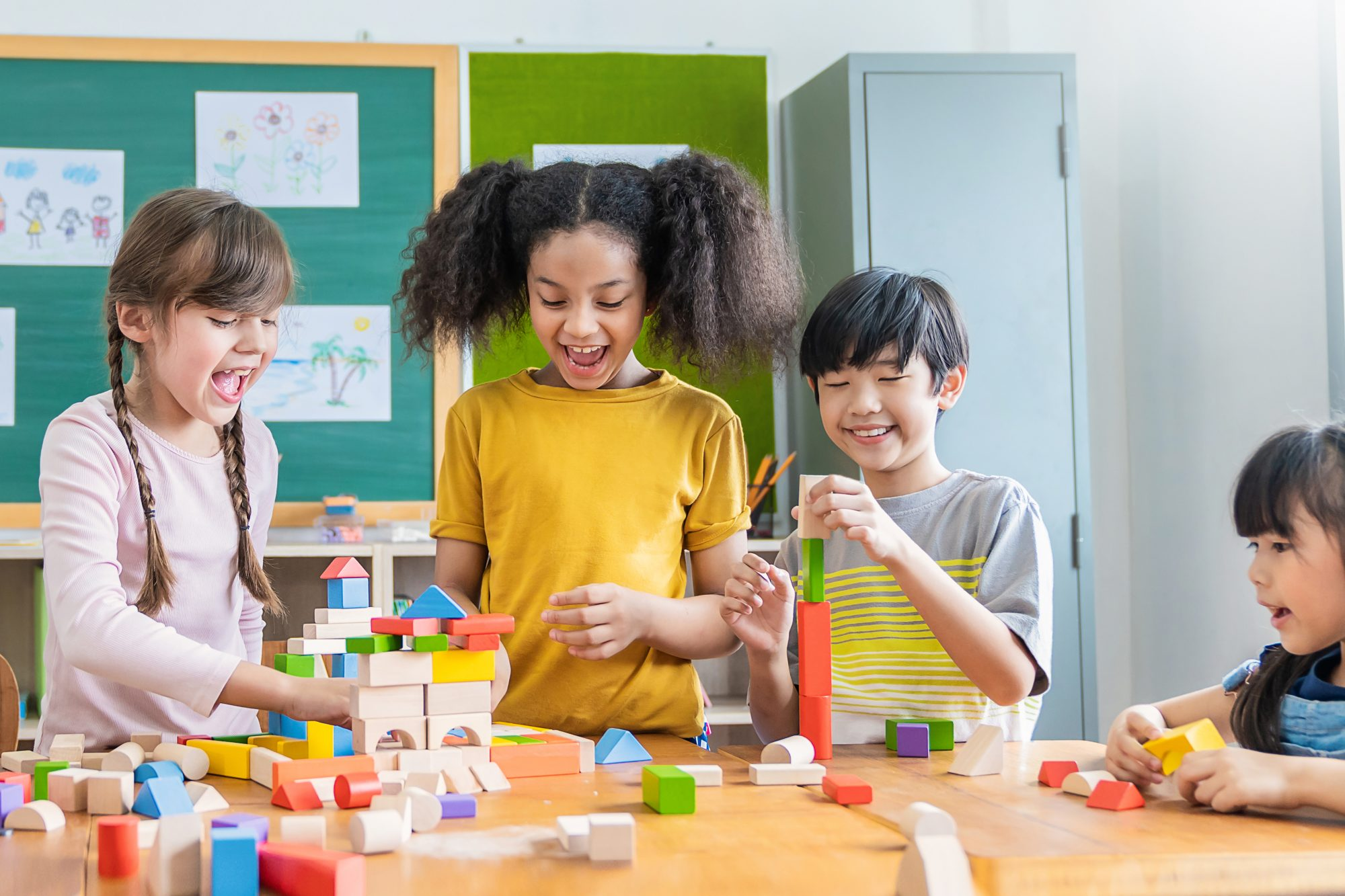 four kids in classroom playing with blocks on table