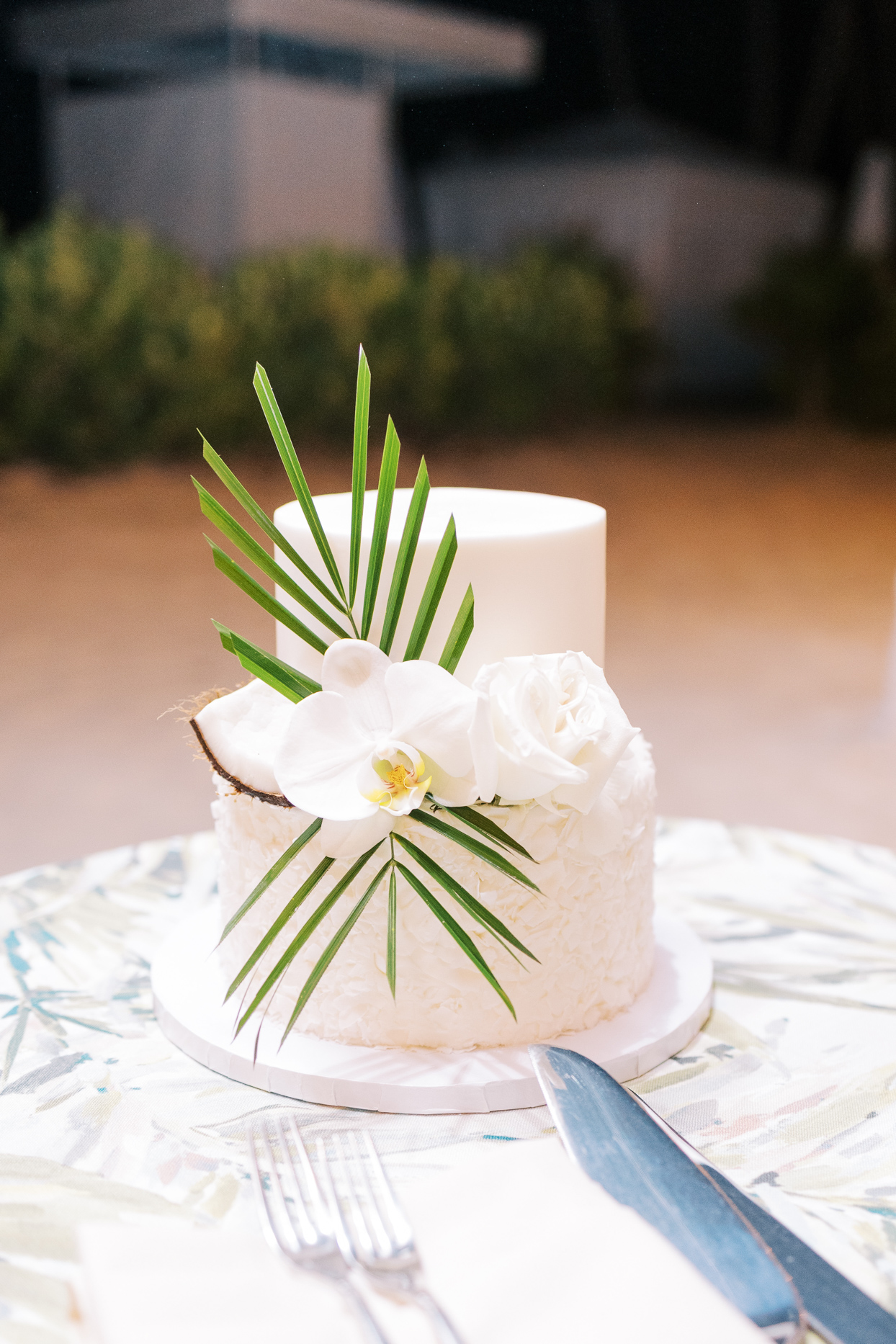 wedding cake with coconut flakes, palm branch, and white orchid