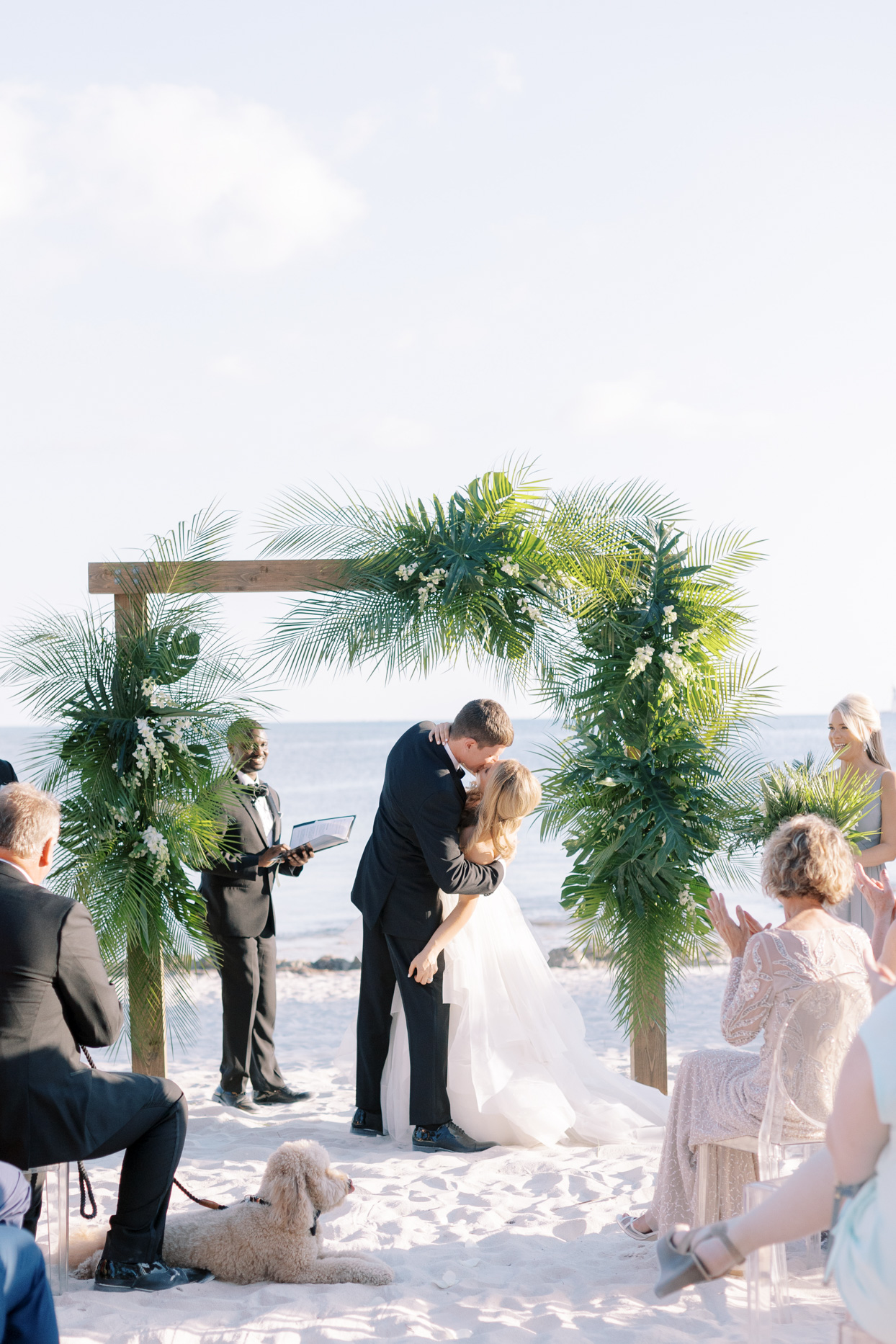 couple kissing under tropical ceremony arch on beach
