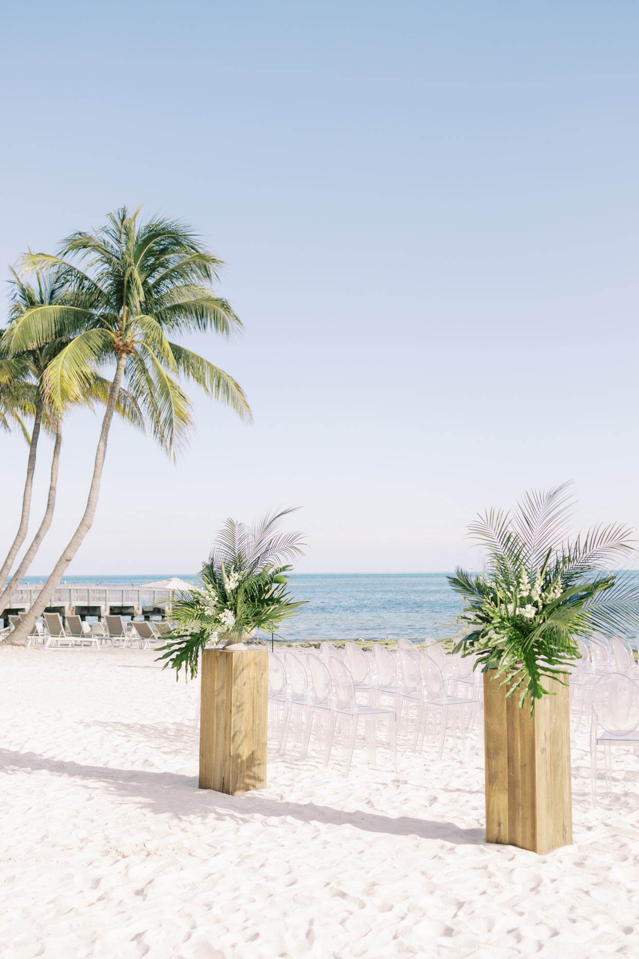 elegant beach wedding set up with clear chairs