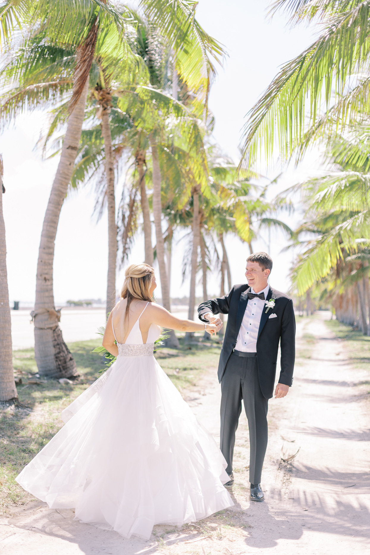 groom spinning bride during first look under palm trees