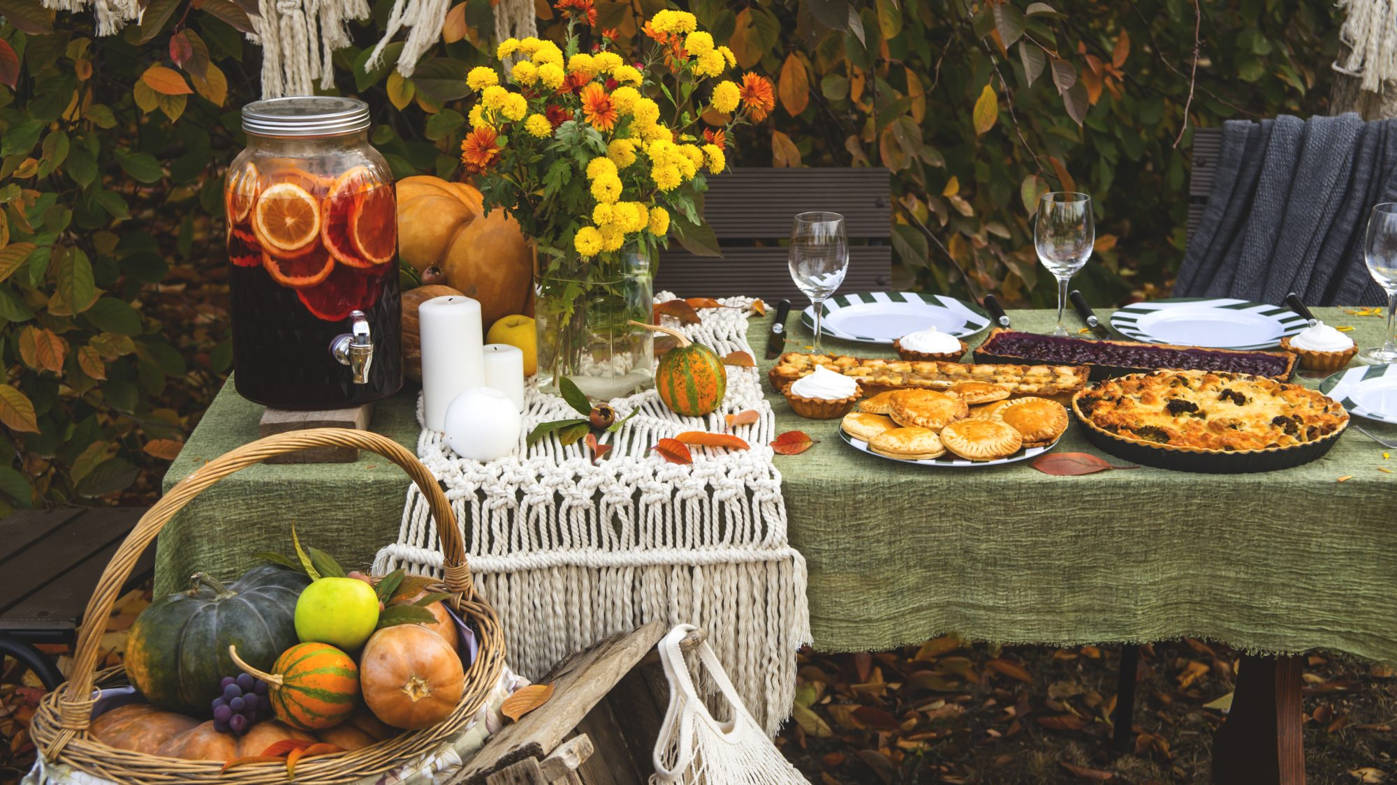 fall brunch table in the backyard with pumpkin and yellow decor.