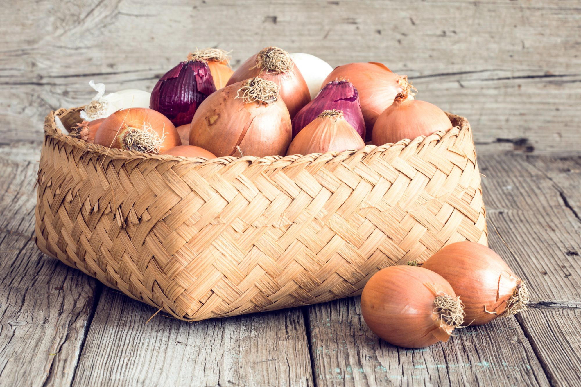 whole raw onions in whicker basket on wood surface