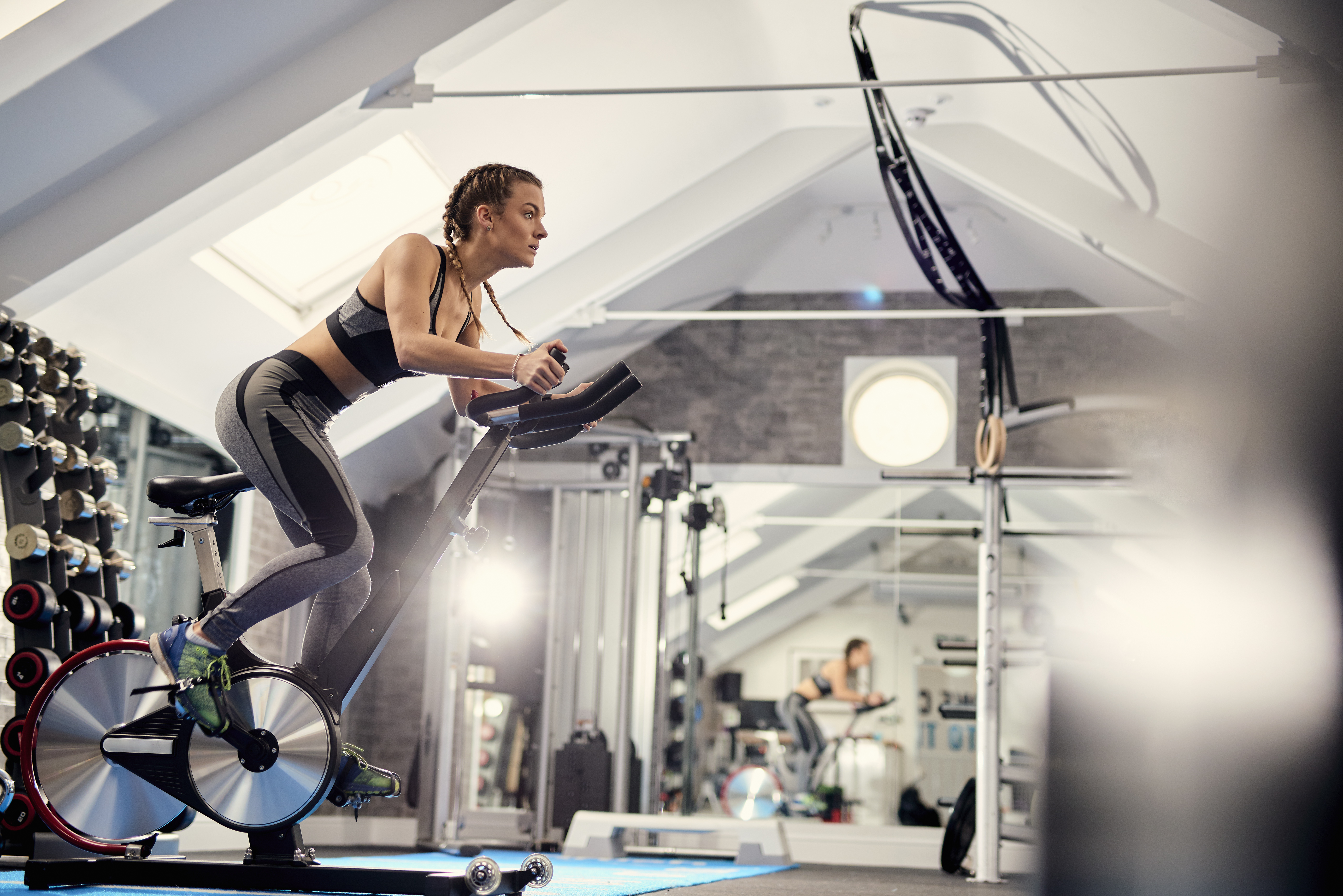 young woman doing spinning workout at the gym