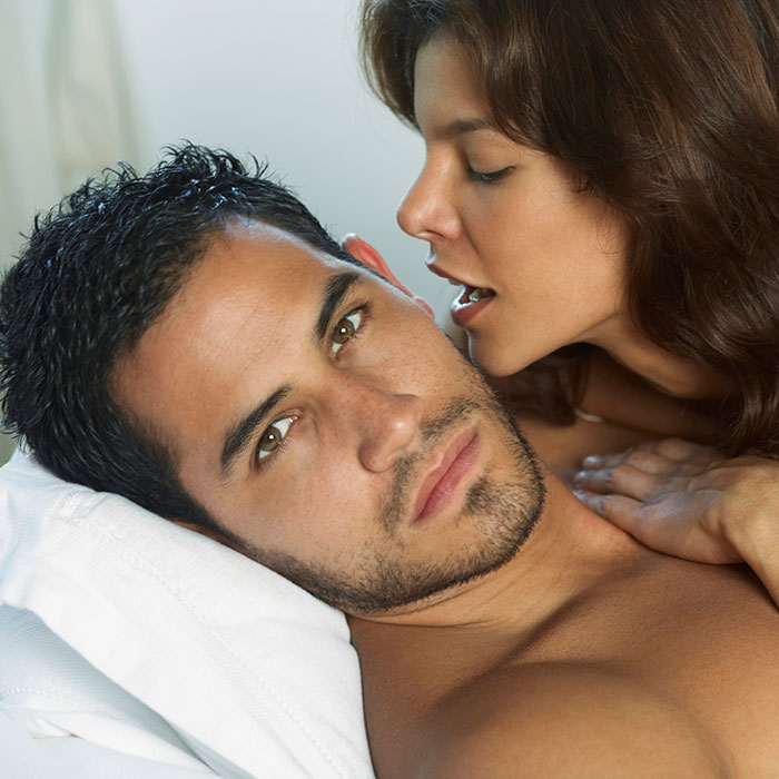 woman-whispering-into-mans-ear-700