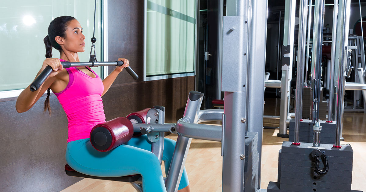 woman-using-lat-pull-down-arm-machine-at-the-gym.jpg