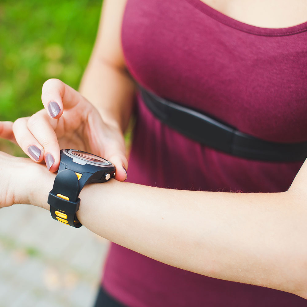 woman running with heart rate monitor to measure running benefits for heart health