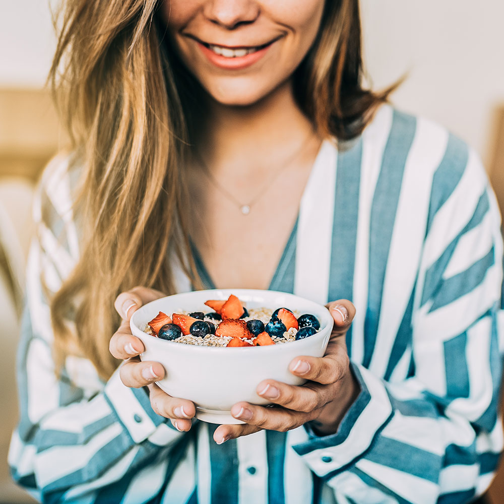 woman with clean eating breakfast oatmeal with berries