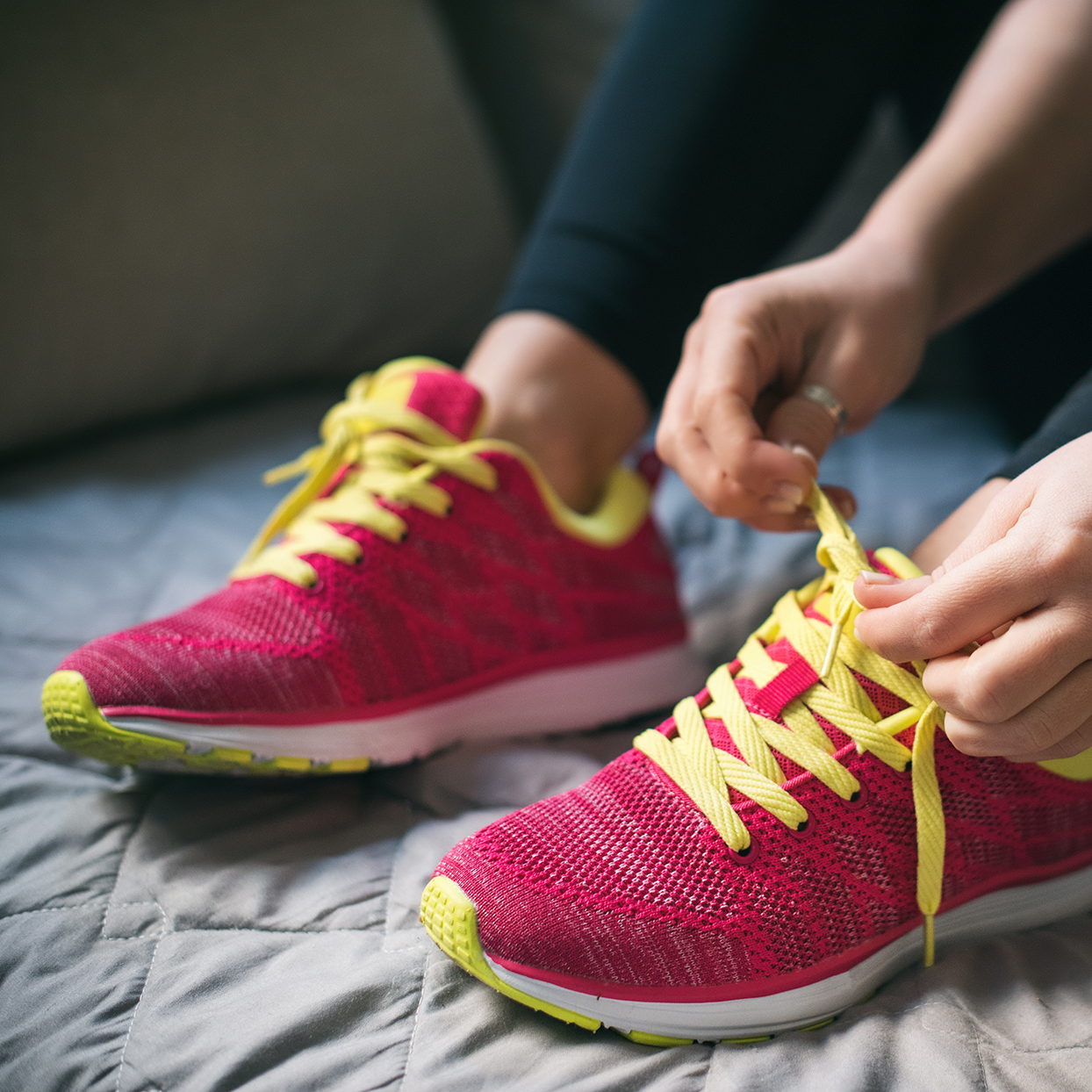 woman-tying-bright-running-shoes