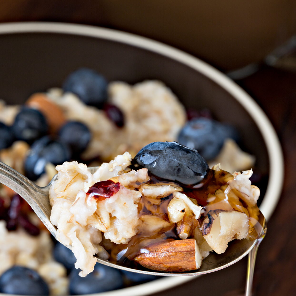 A high angle extreme close up of a spoonful of oatmeal, nuts, blueberry and maple syrup.