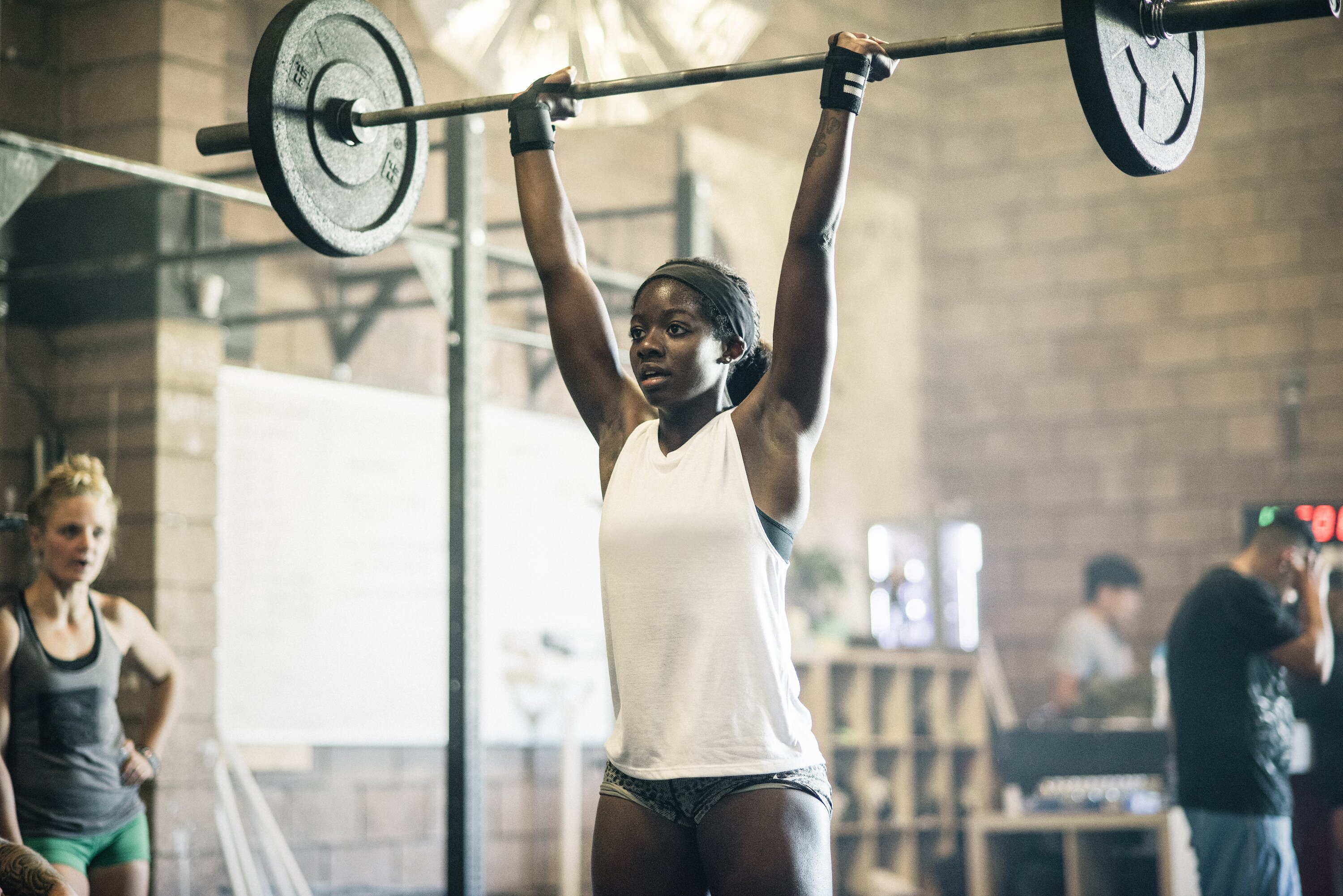 woman burning calories lifting weights in a crossfit gym