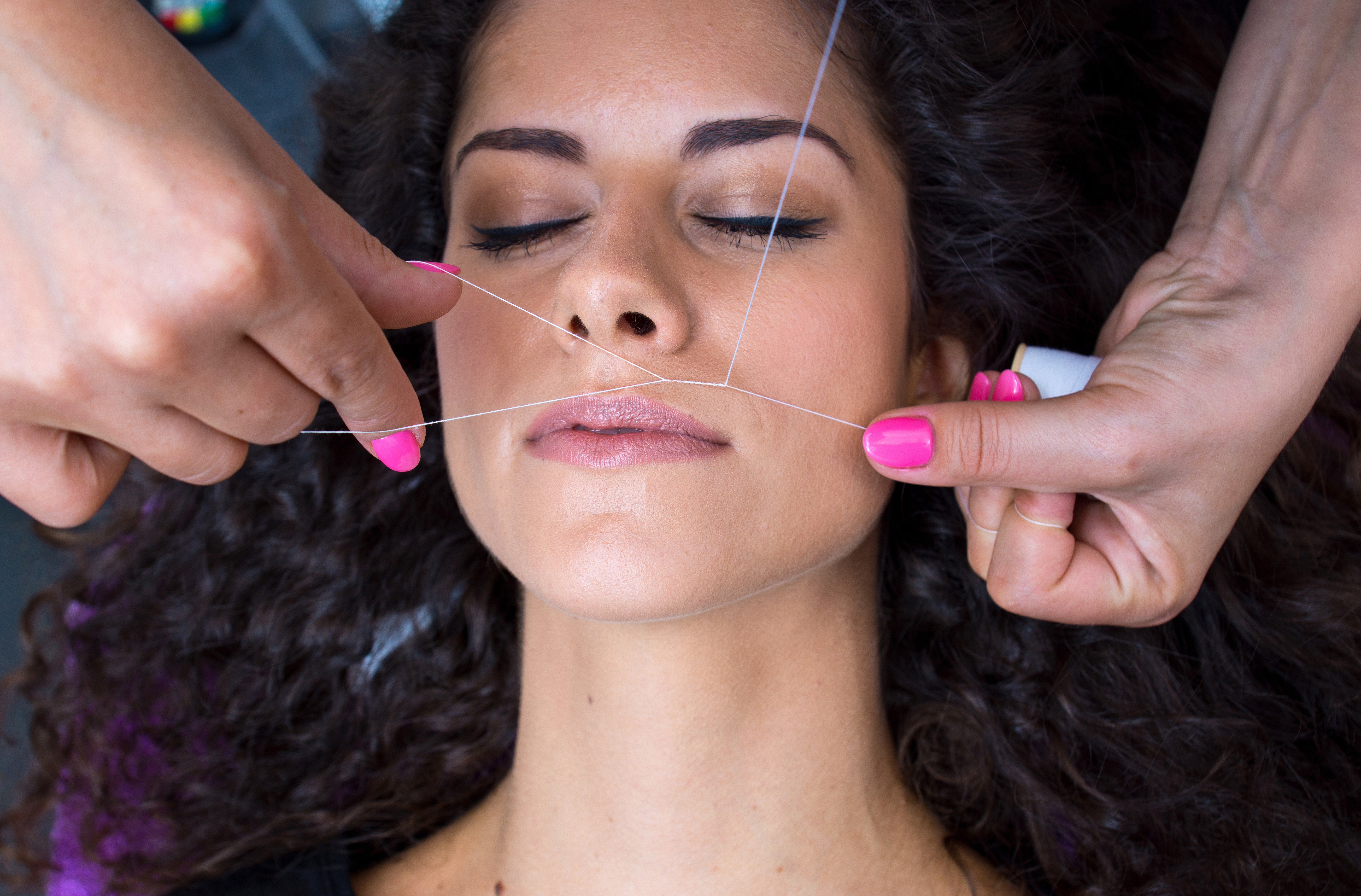 woman getting facial hair removal threading procedure threading