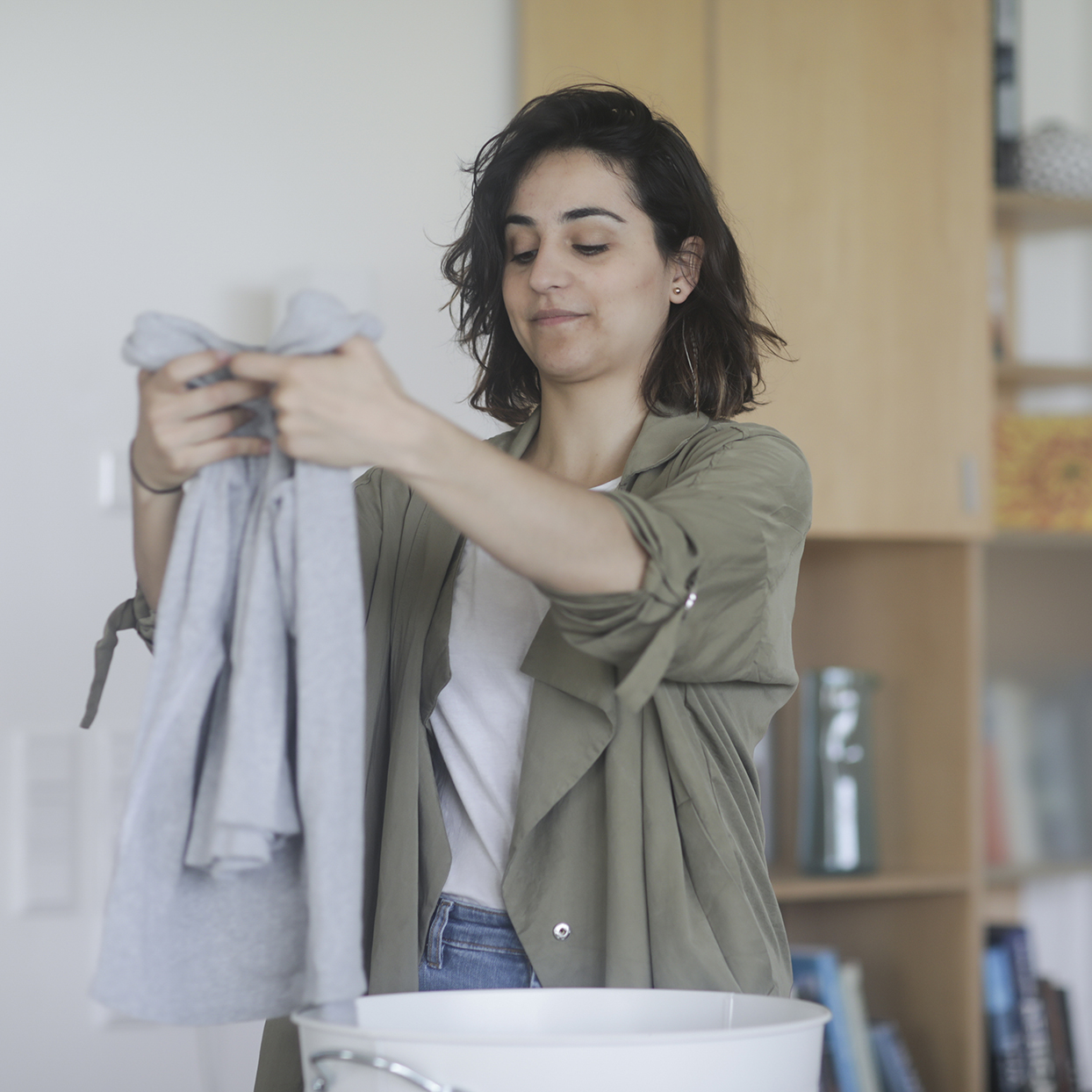 Woman standing in the utility room folding clothing