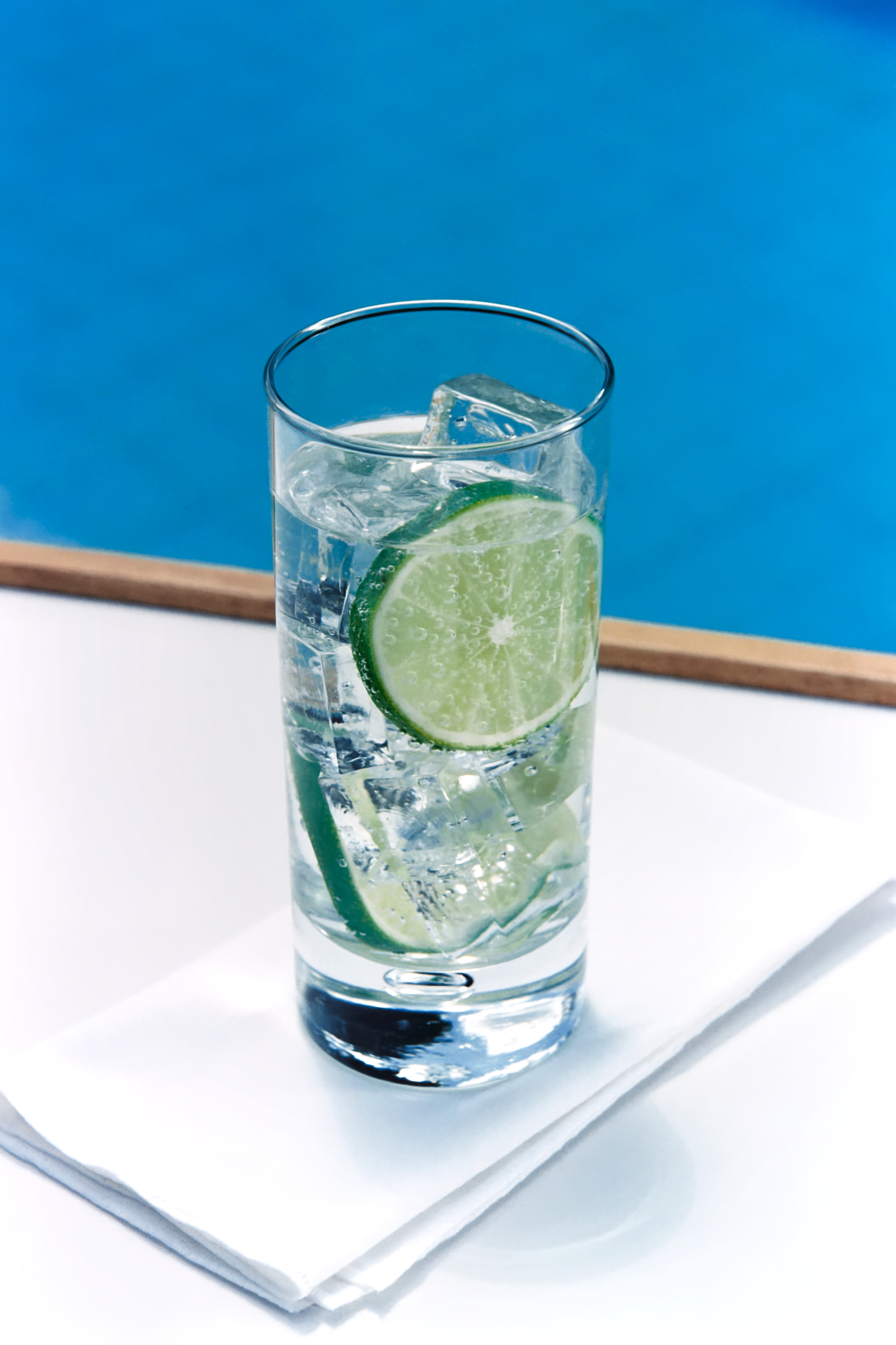 Glass of sparkling water with ice cubes and a slice of lime seltzer health effects