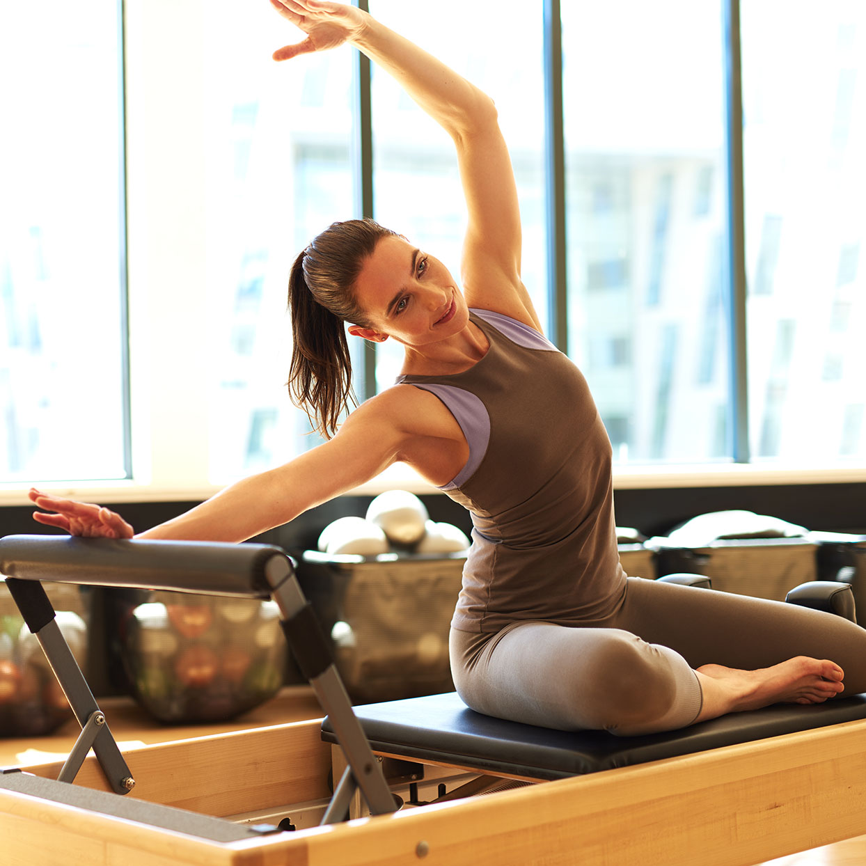 A woman uses a Pilates reformer